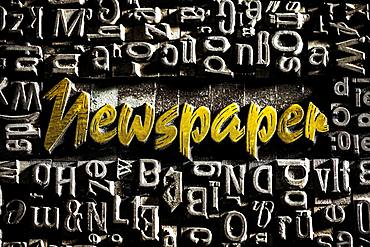 Old lead letters with golden writing show the word Newspaper, Germany, Europe