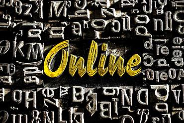 Old lead letters with golden writing show the word Online, Germany, Europe