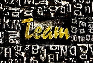 Old lead letters with golden writing show the word team, Germany, Europe