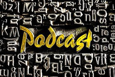 Old lead letters with golden writing show the word podcast