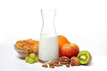 A carafe with milk, bowl with cornflakes, fruits and nuts, Germany, Europe