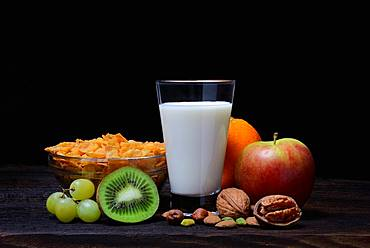 A glass of milk, bowl with cornflakes, fruits and nuts, Germany, Europe