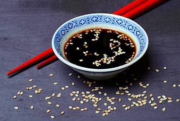 Sesame seeds with soy sauce in small bowls and red chopsticks, Germany, Europe