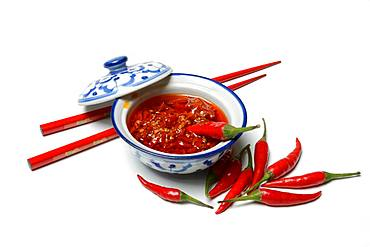 Crushed chilli peppers in oil in shell and red chopsticks, Germany, Europe