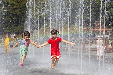 Girls, 4 and 6 years, walking through jets of water from a well, Odongdo Island, Yeosu, Jeollanam-do, South Korea, Asia