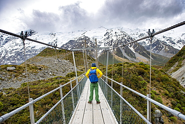 Hiker crosses suspension bridge over Hooker River, Hooker Valley, Mount Cook National Park, Canterbury, New Zealand, Oceania