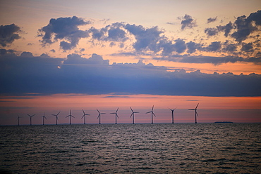 View from Amager beach to wind turbines in the sea at sunrise, offshore wind farm, Copenhagen, Denmark, Europe