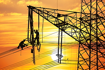 High voltage fitters working on the high voltage pylon at sunset, Baden-Wuerttemberg, Germany, Europe
