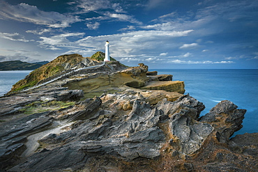 Lighthouse in the evening light on the cliffs of lava rock at Castlepoint, Masterton, Wellington, New Zealand, Oceania