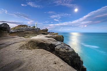 Lighthouse at full moon on the cliffs of lava rock at Castlepoint, Masterton, Wellington, New Zealand, Oceania