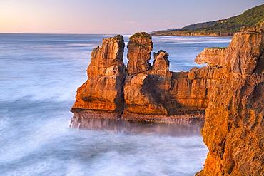Rock formations on the coast of Paparoa National Park in red evening sun, Punakaiki, Runanga, West Coast, New Zealand, Oceania