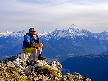 Mountaineer with a snack at the summit Rauher Kopf, Berchtesgadener Alps, behind Watzmann, Bischofswiesen, Berchtesgadener Land, Upper Bavaria, Bavaria, Germany, Europe