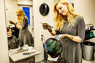 Hairdresser in a hairdressing salon dying strands of hair with aluminium foil, Cologne, North Rhine-Westphalia, Germany, Europe