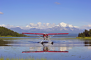 Seaplane Beaver de Havilland lands on a lake off snow-covered mountain Denali, Alaska, USA, North America