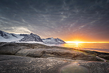 Rocky beach of Tungeneset, snow-covered mountain peaks in the warm sunlight above the sea, stone fjords, Senja Island, Skaland, Troms, Norway, Europe