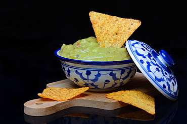 Bowl with guacamole and tortilla chips, Germany, Europe