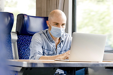 Train ride with mouth protection mask, man working on laptop, Germany, Europe