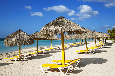 Sunbeds and thatched parasols at the Playa Ancon beach, Trinidad, Cuba, Central America
