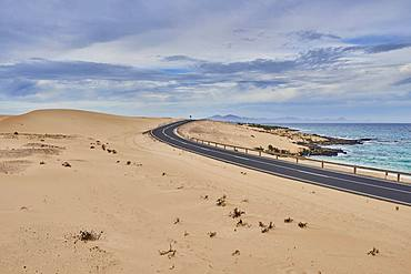 Coastal road through sand dunes, Parque Natural de Corralejo, Fuerteventura, Canary Islands, Spain, Europe