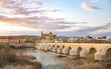 Sunset, Puente Romano, Roman bridge over Rio Guadalquivir, behind Mezquita, Catedral de Cordoba, Cordoba, Andalusia, Spain, Europe