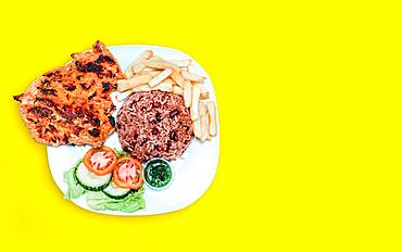 Nicaraguan food plate with yellow background with copy space, chicken plate with potatoes and salad with yellow background