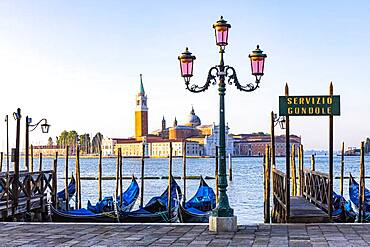 Lantern and parked gondolas at the end of Piazza San Marco with a view of the Basilica of San Giorgio Maggiore, Venice, Veneto, Italy, Europe