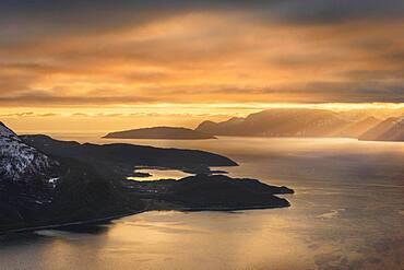 Dramatic cloud atmosphere with sunshine at the KvaenangenFjord, Sorstraumen, Troms, Norway, Europe