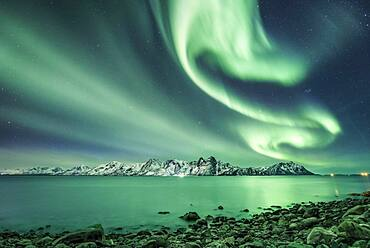 Northern lights over the sea and snow-covered mountains, Vesteralen, Nordland, Norway, Europe