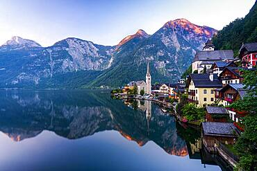 Local view of Hallstatt and the protestant church at sunrise, reflected in the lake Hallstatt, Salzkammergut, Dachstein region, Upper Austria, Austria, Europe