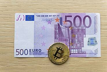 Symbol image digital currency, physical coin Bitcoin, on euro banknote