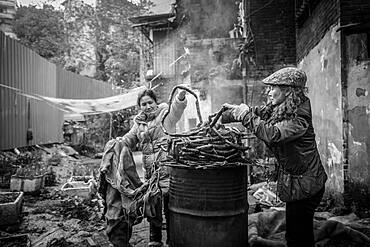 Street scene in an old town quarter of Chongqing. Women are smoking homemade sausages. These districts are gradually being demolished to make room for new residential areas with high-rise buildings, Chongqing, China, Asia