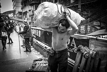Bang-bang carriers in a market at the port of Chongqing, the carriers are like a caste of their own, carrying loads for the traders for little money, mostly immigrant workers from rural areas, Chongqing, China, Asia