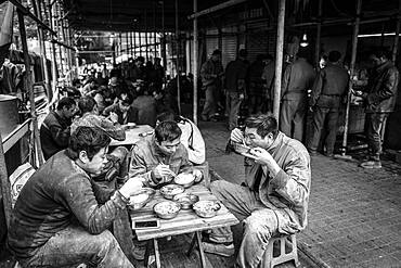 Worker having lunch at a stall in a market in the center of Chongqing, from his wages he can only buy the cheap pieces of meat, Chongqing, China, Asia