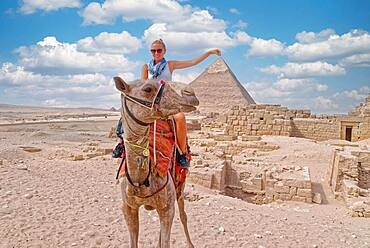 Woman on a camel in front of a pyramid, Giza, Cairo, Egypt, Africa