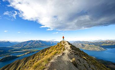 Hiker stands at the summit, view of mountains and lake from Mount Roy, Roys Peak, Lake Wanaka, Southern Alps, Otago, South Island, New Zealand, Oceania