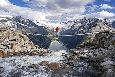 Hiker, woman on suspension bridge at the Olpererhuette, Schlegeis reservoir, Schlegeis reservoir, Zillertal Alps, Schlegeiskees glacier, Zillertal, Tyrol, Austria, Europe