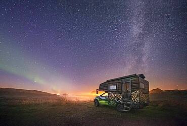 Night shot of a painted camper van under the Milky Way with northern lights, Gimsoy, Lofoten, Nordland, Norway, Europe