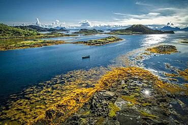 Fjord landscape with small rock islands at low tide with yellow seaweed, small wooden boat between archipelagos in the sea, Lodingen, Nordland, Lofoten, Norway, Europe