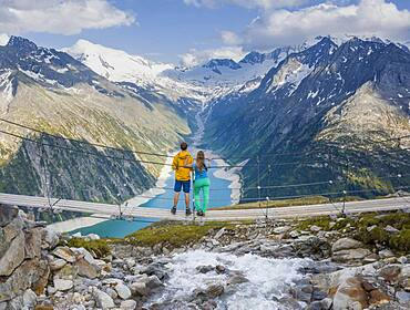 Hiker, young woman and young man on suspension bridge at the Olpererhuette, Schlegeis reservoir, Schlegeis reservoir, Zillertal Alps, Schlegeiskees glacier, Zillertal, Tyrol, Austria, Europe