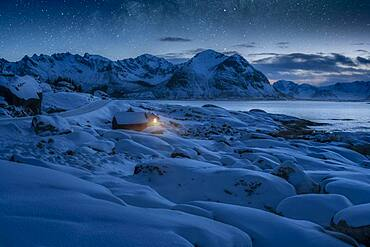 Deep snowy winter landscape by the sea, wooden cabin with warm light on the coast, behind mountains under starry sky, Kleppstad, Nordland, Lofoten, Norway, Europe