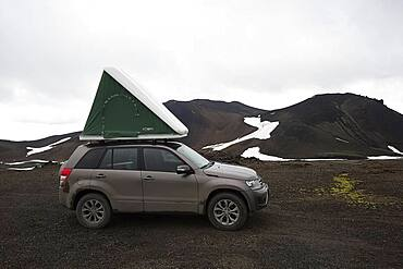 Off-road vehicle with roof tent in the mountains, barren volcanic landscape with snowfields, Snaefellsjoekull, Snaefellsjoekull, Snaefellsnes peninsula, Snaefellsnes, Iceland, Europe