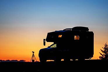 Silo hut motorhome and photo tripod with camera bag and camera at dusk, Nordland, Norway, Europe