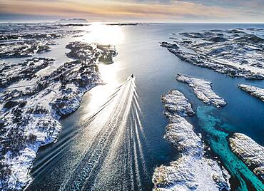 Motorboat sailing through a winter fjord landscape with small islands, Heroy, Nordland, Norway, Europe