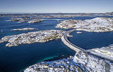 Aerial view, country road through the sea connects populated, small, winterly islands with the mainland, behind mountains, Heroy, Nordland, Norway, Europe