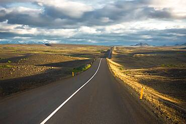 Road in the evening light runs through vuclan plateau with lava rock in the Krafla, Myvatn region, Skutustaoir, Norourland eystra, Iceland, Europe