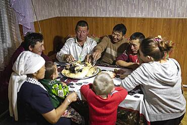 Spai Bashakhan, head of a nomadic family in the Altai mountains, dinner together in the winter quarters, Olgii province, Mongolia, Asia