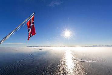 Norwegian flag waving over fjord in Greenland, East Coast, Denmark, Europe