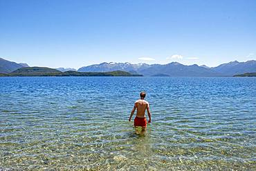 Young man bathes in the lake, Lake Manapouri, Frasers Beach, Manapouri, South Island, New Zealand, Oceania