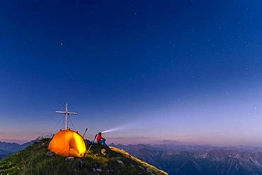 Cross of the Kreuzspitze by a starry sky with tent and mountaineer at the summit, in the background the Lechtal Alps, Elmen, Lechtal Alps, Ausserfern, Tyrol, Austria, Europe
