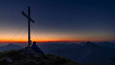 Cross of the Kreuzspitze at sunrise with mountaineer at the summit, in the background the Lechtal Alps, Elmen, Lechtal Alps, Ausserfern, Tyrol, Austria, Europe